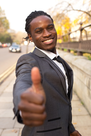 ok symbol: young business man showing a thumbs up gesture.