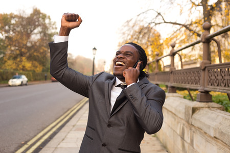 american banker: Business man celebrating on the phone. Stock Photo