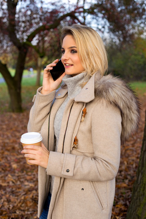young woman talking on the phone with a coffee photo