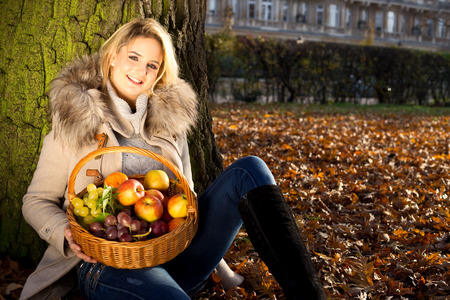 young woman sitting in a park with a basket of fruit. photo