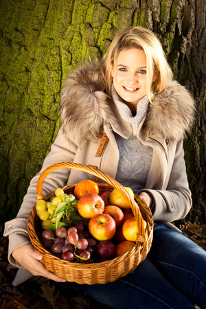 young woman holding a basket of fruit in a park photo