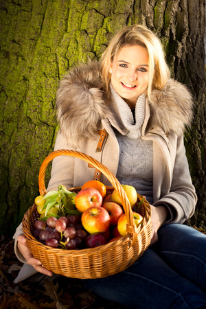 young woman sitting in a park holding a basket of fruit. photo