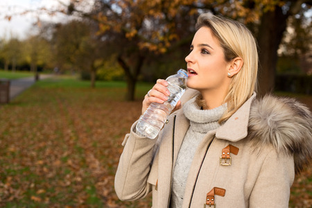 young woman drinking water in a park