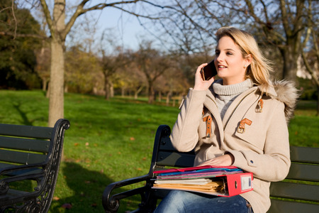 woman sitting on a park bench with folders and talking on the phone photo