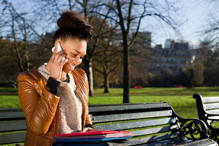 young woman talking on the phone in the park photo