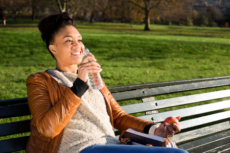 fruit in water: young woman holding a water bottle and a apple Stock Photo