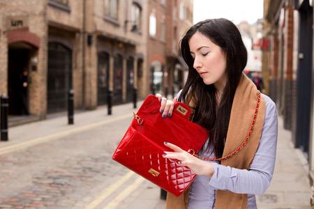 jonge vrouw zoekt in haar tas