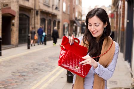 handbag: woman looking in handbag Stock Photo