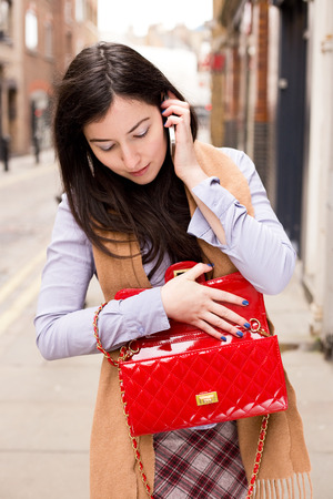 young caucasian: young woman looking in her bag while on the phone Stock Photo