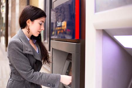 jonge vrouw het opnemen van geld bij de ATM. Stockfoto