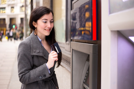 young woman showing her card at the cash machine. photo
