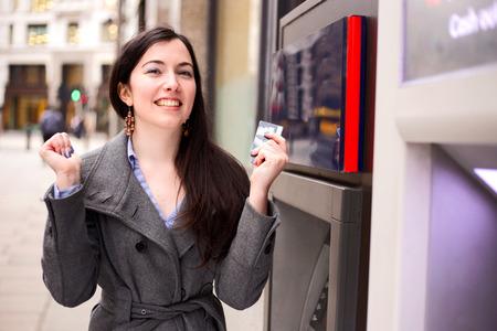 젊은 여자가 현금 기계에서 축하