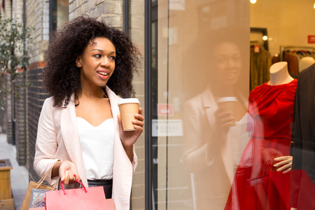 young woman with shopping bags and a coffee photo