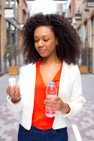 african american woman checking her pills and holding a bottle of water. photo