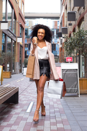 young woman walking with a coffee and shopping bags photo