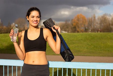 a fit young woman holding excersise mat and bottle of water