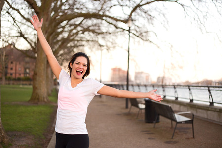 fitness goal: happy woman outdoors celebrating a fitness goal.