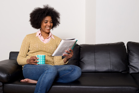 a young woman reading a magazine with a coffee at home. photo