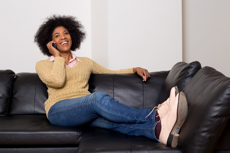 young african american woman talking on the phone at home photo