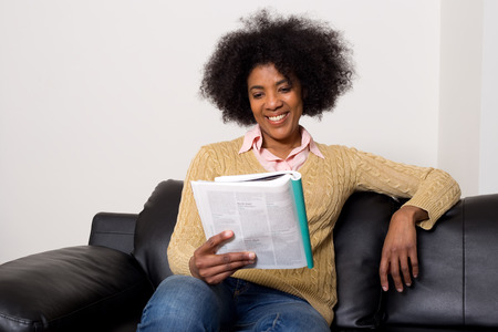 young woman sitting on her sofa reading a magazine Stock Photo