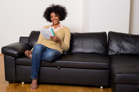 young woman reading a magazine at home photo
