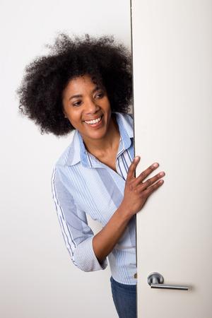 abrir puertas: una mujer joven que mira alrededor de una puerta Foto de archivo