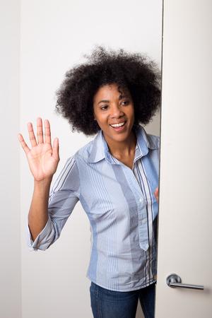 a young woman waving goodbye at the door photo