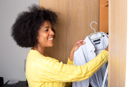 a young woman at home taking a shirt out of a wardrobe for her man.