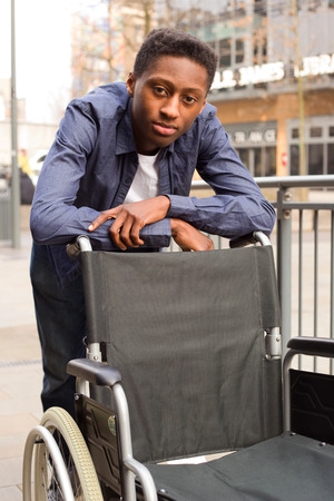 man in chair: a young man standing next to a wheelchair, volunteer, carer.