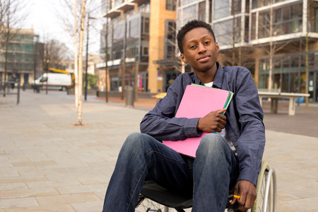 young disabled student sitting in a wheelchair  holding folders Standard-Bild