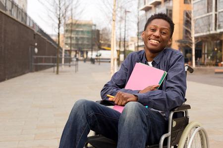 estudiantes medicina: feliz joven discapacitado en un archivo de carpetas celebración de sillas de ruedas.