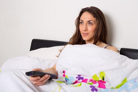 mujer viendo tv: joven mujer viendo la televisi�n en su dormitorio. Foto de archivo