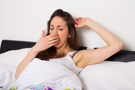 tired woman yawning and stretching in bed photo