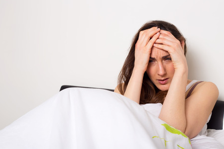 person sitting: mujer tensionada al sufrimiento a casa de un dolor de cabeza