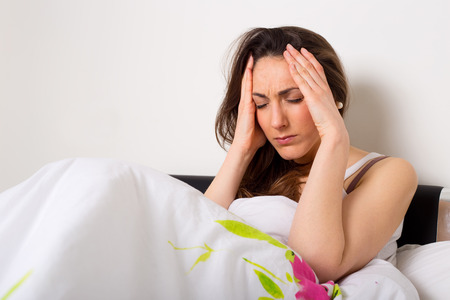 young woman at home suffering from a headache photo