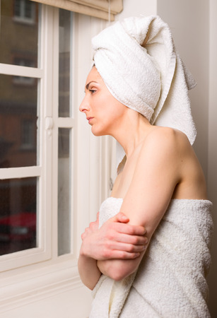 looking out: young woman looking out of a window after a shower.