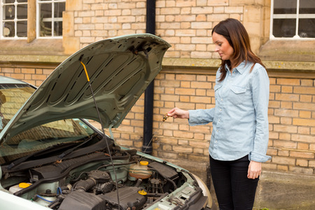 gage: young woman checking the oil gage on her car Stock Photo