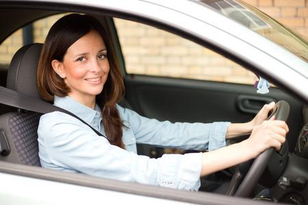 cinturon de seguridad: Mujer joven conduc�a su autom�vil con el cintur�n de seguridad abrochado Foto de archivo