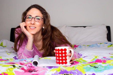adult magazine: beautiful young woman lying on her bed with coffee and magazine Stock Photo