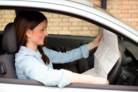 young woman reading a map in her car photo
