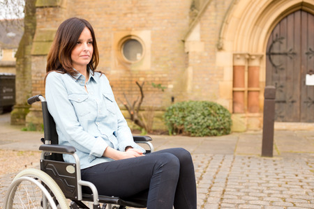a young woman in a wheelchair looking sad photo