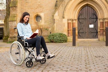 a young wheelchair user reading a bible photo