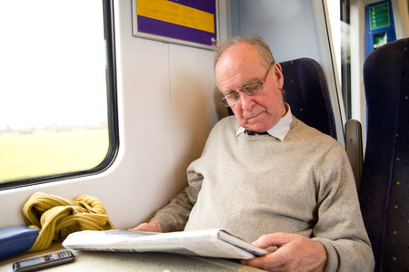 old man reading the newspaper on the train photo