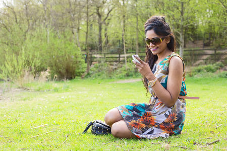 indian summer seasons: young woman sitting on the grass checking her text message