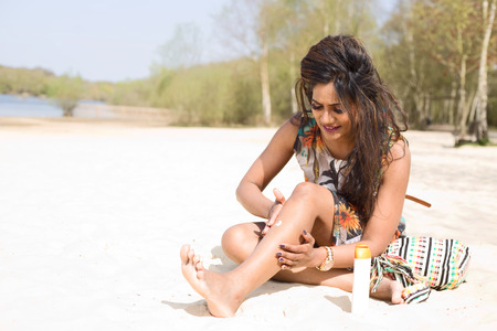 sun care: young woman applying suncream at the beach