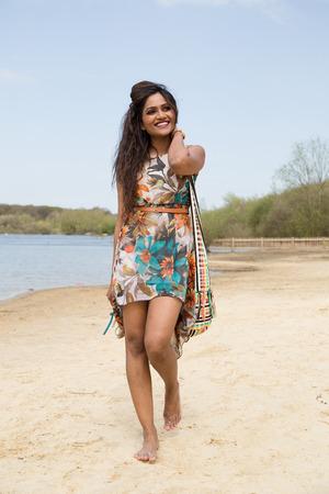 a young indian girl walking along the river bank photo