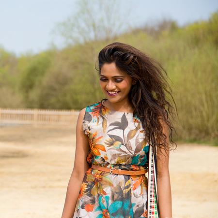 young indian woman walking along the river bank photo