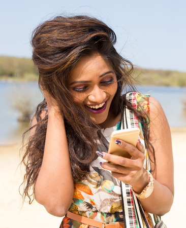 laughing girl: young indian woman checking her text messages