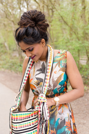 beautiful indian girl face: young woman looking in her handbag