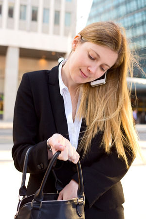 business woman searching in her handbag whilst on the phone photo